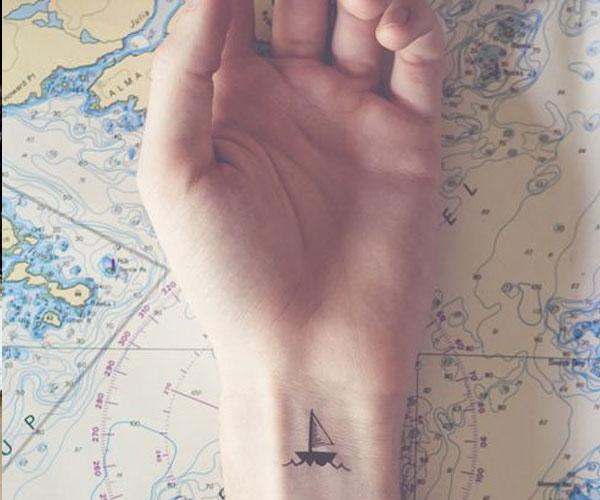 Sencillo tatuaje de un barco en la muñeca
